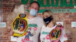 Competitive eaters Joey Chestnut, left, and Miki Sudo, right, pose for a photograph after winning their respective divisions with new world records after the Nathan's Famous July Fourth hot dog eating contest, Saturday, July 4, 2020, in the Brooklyn borough of New York. (AP Photo/John Minchillo)