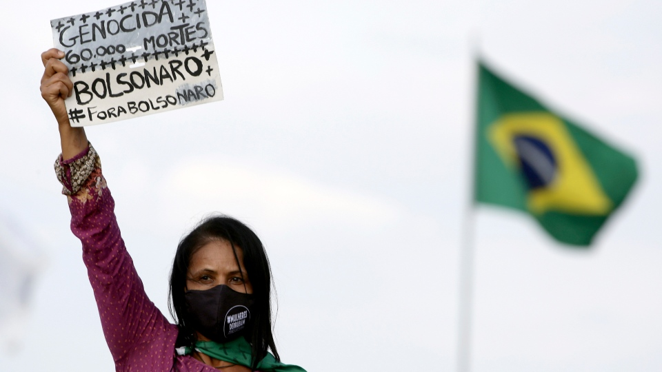 A women's movement activist holds a sign that reads in Portuguese