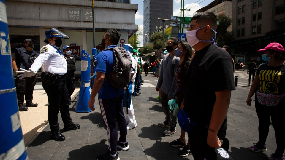 A Mexican police officer gives social-distancing and precautionary COVID-19 related guidelines to tourists in the historic center of Mexico City, Friday, July 3, 2020. Limited reopening of restaurants and other businesses in the capital this week came as new coronavirus cases continued to climb steadily. (AP Photo/Fernando Llano)