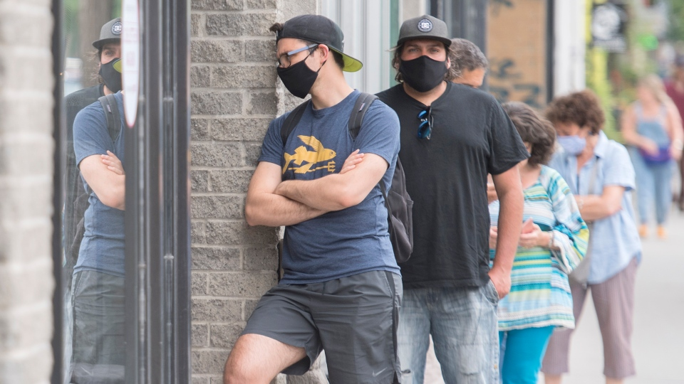 People wear face masks as they wait to enter a store in Montreal, Saturday, June 27, 2020, as the COVID-19 pandemic continues in Canada and around the world. (THE CANADIAN PRESS/Graham Hughes)