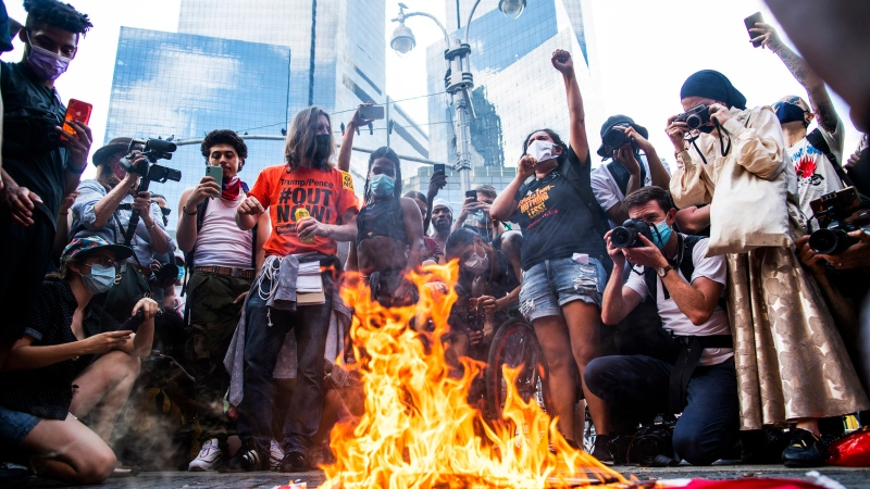 Protesters burn U.S. flags during a protest near Trump International Hotel, Saturday, July 4, 2020, in New York. (AP Photo/Eduardo Munoz Alvarez)