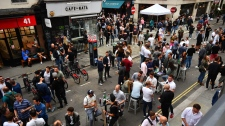 Drinkers in Soho congregate, as coronavirus lockdown restrictions eased across the country, in London, Saturday July 4, 2020. (Victoria Jones/PA via AP)
