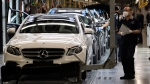 Workers inspect newly assembled cars at a Beijing Benz Automotive Co. Ltd factory, a German joint venture company for Mercedes-Benz, in Beijing on Wednesday, May 13, 2020. (AP Photo/Ng Han Guan)