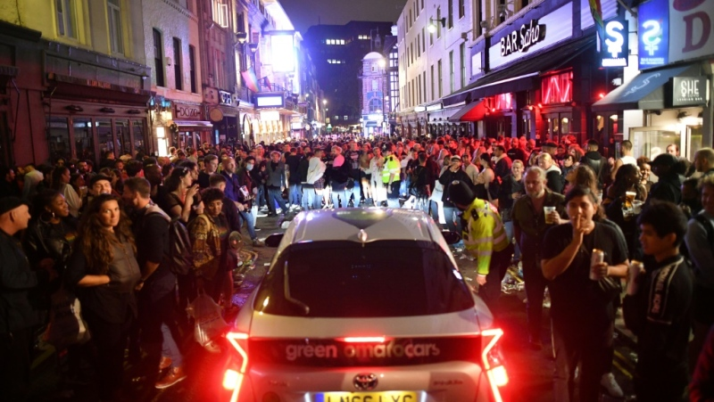 A car tries to drive along a street filled with people drinking in the Soho area of London. (AFP)