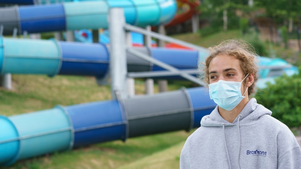 A lifeguard wears a protective mask next to a water slide in Bromont, Que. on Monday, June 29, 2020 as water parks reopen in the province of Quebec. THE CANADIAN PRESS/Paul Chiasson
