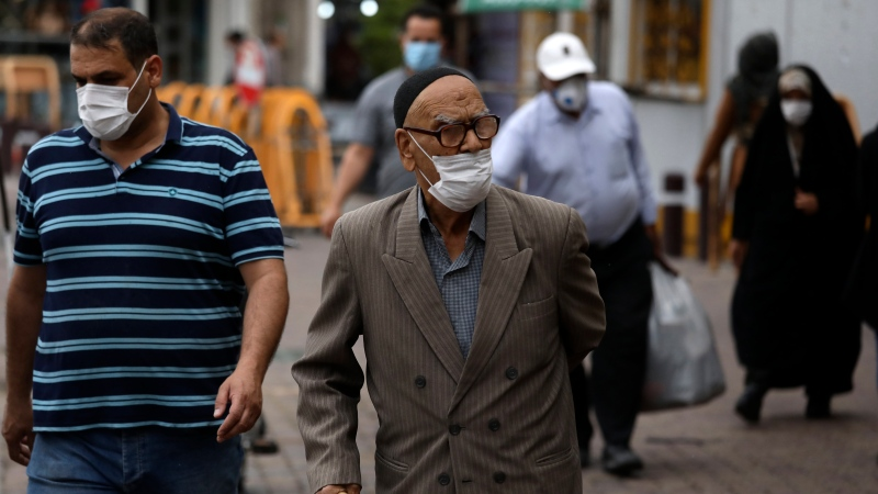 People wearing protective face masks to help prevent the spread of the coronavirus walk on a sidewalk in the city of Zanjan, some 330 kilometers west of the capital Tehran, Iran, Sunday, July 5, 2020. (AP Photo / Vahid Salemi)