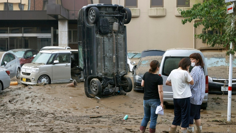 A car stands vertically on a muddy road after being washed away by flood, in Hitoyoshi, Kumamoto prefecture, southwestern Japan, Sunday, July 5, 2020. (Kyodo News via AP)