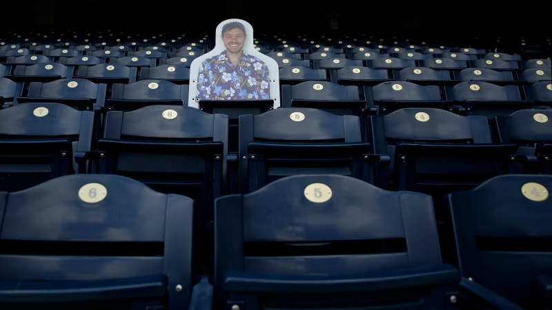 A cutout photo of a fan is seen alone is a section of seats during Kansas City Royals baseball practice at Kauffman Stadium Friday, July 3, 2020 in Kansas City, Mo. (AP Photo/Charlie Riedel)