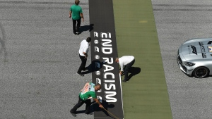 Workers prepare a sticker reading 'End Racism' on the track before the Austrian Formula One Grand Prix race at the Red Bull Ring racetrack in Spielberg, Austria, Sunday, July 5, 2020. (Joe Klamar/Pool via AP)