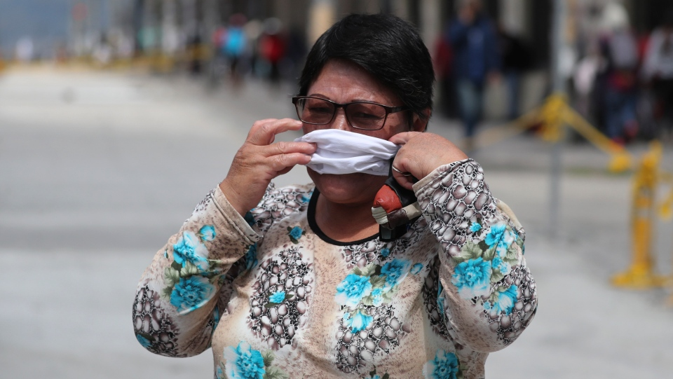 A woman hurriedly places a protective face mask over her mouth and nose in Quito, Ecuador, Wednesday, June 10, 2020. (AP Photo/Dolores Ochoa)