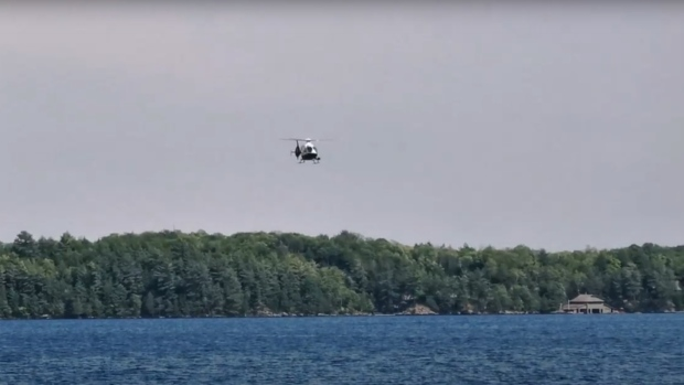 An OPP helicopter searches for a missing paddler on Lake Muskoka in Muskoka Lakes, Ont. on Sun. July 5, 2020 (Don Wright/CTV News)