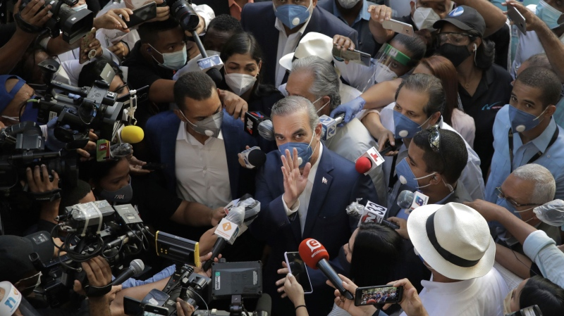 Luis Abinader, presidential candidate of the opposition Modern Revolutionary Party, greets the crowd while he is surrounded by journalists at a voting center during the presidential elections, in Santo Domingo, Dominican Republic, Sunday, July 5, 2020. (AP Photo/Tatiana Fernandez)