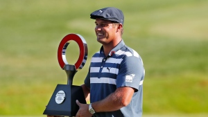 Bryson DeChambeau holds the Rocket Mortgage Classic golf tournament trophy Sunday, July 5, 2020, at Detroit Golf Club in Detroit. DeChambeau won the tournament. (AP Photo/Carlos Osorio)