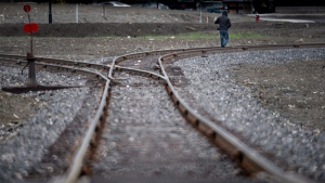 A man walks down the tracks in downtown of Lac-Megantic, Que Tuesday, June 10, 2014, where an oil-filled train screeched off the tracks and exploded killing 47 people. (THE CANADIAN PRESS/Paul Chiasson)