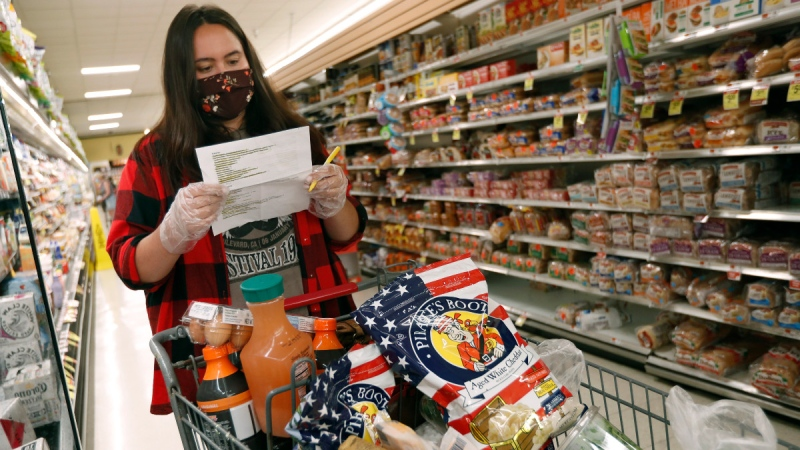 Alexandra Lopez-Djurovic checks her shopping list as she shops for a client in an Acme supermarket in Bronxville, N.Y., on July 1, 2020. (Kathy Willens / AP)