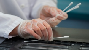 Employees work at the Canadian Hospital Specialities (CHS) helping take dual COVID-19 testing swab kits and separating them into two units to help with swab capacity during the COVID-19 pandemic in Oakville, Ont., on Monday, June 8, 2020. (Nathan Denette/The Canadian Press)