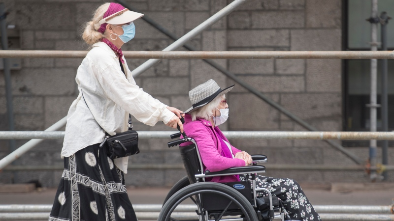 A woman wears a face mask as she pushes another woman in a wheelchair in Montreal, Sunday, July 5, 2020, as the COVID-19 pandemic continues in Canada and around the world. THE CANADIAN PRESS/Graham Hughes