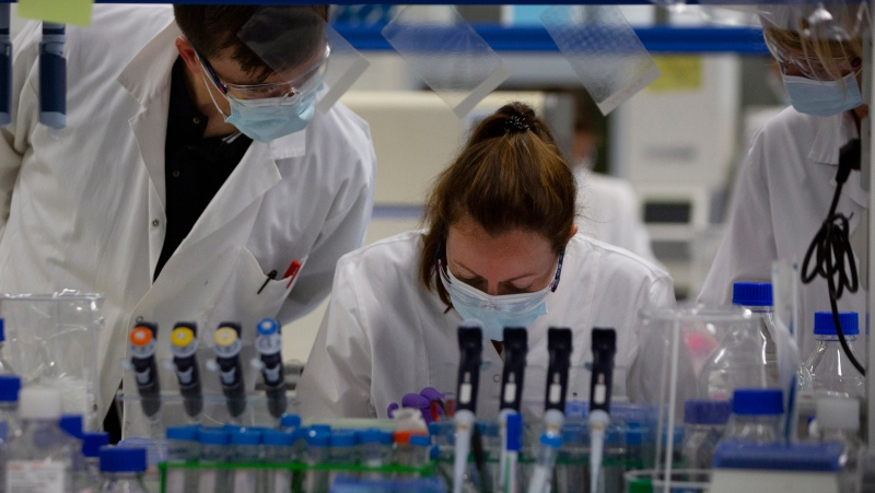 Lab technicians speak with each other during research on coronavirus, COVID-19, at Johnson & Johnson subsidiary Janssen Pharmaceutical in Beerse, Belgium, Wednesday, June 17, 2020. (AP Photo/Virginia Mayo)