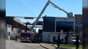 An aerial ladder truck douses hotspots on the roof of IMT Standen's warehouse on July 6, 2020 following a morning fire