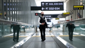 "A man rides a escalator wearing mandatory masks at Toronto's Pearson International Airport for a ""Healthy Airport"" during the COVID-19 pandemic in Toronto on Tuesday, June 23, 2020. THE CANADIAN PRESS/Nathan Denette"