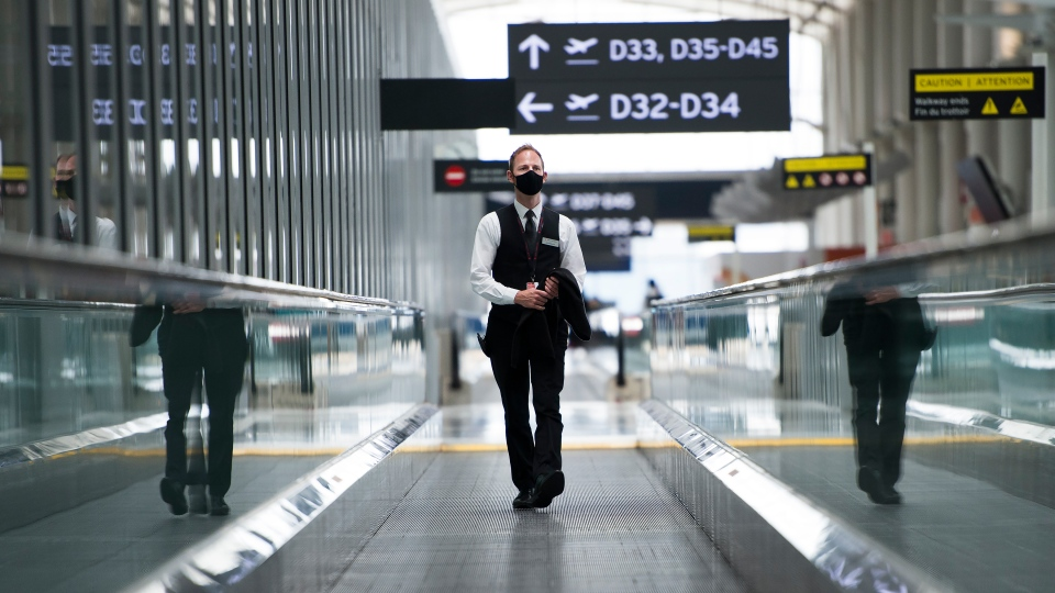 A man rides a escalator wearing mandatory masks at Toronto's Pearson International Airport for a
