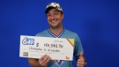Christopher Howell-Harries of London Ont. holds his winnings in LOTTO 6/49. (Supplied)