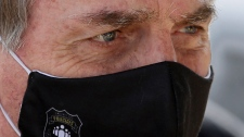 In this May 26, 2020 file photo, Brazil's President Jair Bolsonaro, wearing a face mask with a logo of the Federal Police, leaves his official residence of Alvorada Palace in Brasilia, Brazil. (AP Photo/Eraldo Peres, FIle)