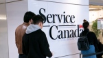 In this file image, people line up at a Service Canada office in Montreal on Thursday, March 19, 2020. THE CANADIAN PRESS/Paul Chiasson