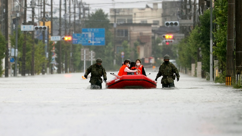Japan Self Defense Force members rescue residents on a rubber boat on a flooded road hit by heavy rain in Omuta, Fukuoka prefecture, southern Japan Tuesday, July 7, 2020. Rescue operations continued and rain threatened wider areas of the main island of Kyushu. (Juntaro Yokoyama/Kyodo News via AP)