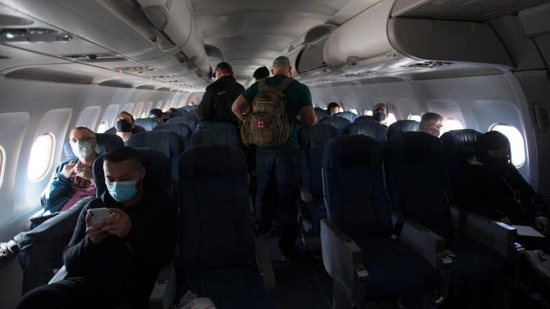 Passengers wear protective face masks and are physically distanced on a flight from Calgary to Vancouver, Tuesday, June 9, 2020. THE CANADIAN PRESS/Jonathan Hayward