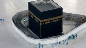 FILE - In this March 7, 2020 file photo, workers disinfect the ground around the Kaaba, the cubic building at the Grand Mosque, over fears of the new coronavirus, the Muslim holy city of Mecca, Saudi Arabia. (AP Photo/Amr Nabil, File)