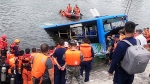 In this photo released by Xinhua News Agency, rescuers watch as a bus that fell into a lake is recovered in the Xixiu District of Anshun, southwestern China's Guizhou Province, Tuesday, July 7, 2020. (Long Rui/Xinhua via AP)