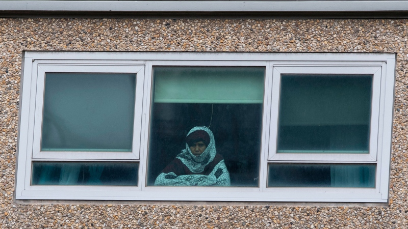 A woman looks out a window from a locked-down public housing tower in Melbourne, Monday, July 6, 2020. (AP Photo/Andy Brownbill)