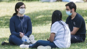 People wear face masks as they gather in a city park in Montreal, Wednesday, July 1 2020, as the COVID-19 pandemic continues in Canada and around the world. THE CANADIAN PRESS/Graham Hughes