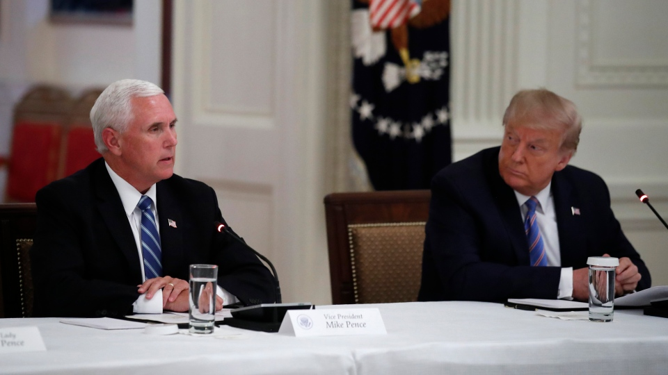 President Donald Trump listens as Vice President Mike Pence speaks during a