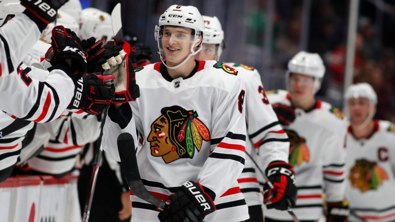 In this file photo, Chicago Blackhawks left wing Dominik Kubalik, center, smiles during a game against the Colorado Avalanche during the third period of an NHL hockey game Saturday, Dec. 21, 2019, in Denver. (AP Photo/David Zalubowski)