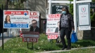 A women wearing a mask walks past real estate listings during the COVID-19 pandemic in Mississauga, Ont., on Tuesday, May 26, 2020. Health officials and the government have asked that people stay inside to help curb the spread of COVID-19. THE CANADIAN PRESS/Nathan Denette