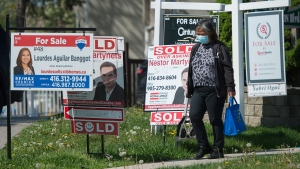 A woman wearing a mask walks past real estate listings during the COVID-19 pandemic in Mississauga, Ont., on Tuesday, May 26, 2020. Health officials and the government have asked that people stay inside to help curb the spread of COVID-19. THE CANADIAN PRESS/Nathan Denette