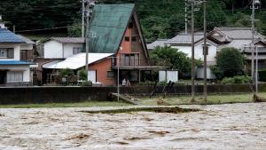People look at swollen Hida river following heavy rain in Gero, Gifu prefecture, southern Japan Wednesday, July 8, 2020. Floodwaters flowed down streets in southern Japanese towns hit by heavy rains. (Yuya Shino/Kyodo News via AP)