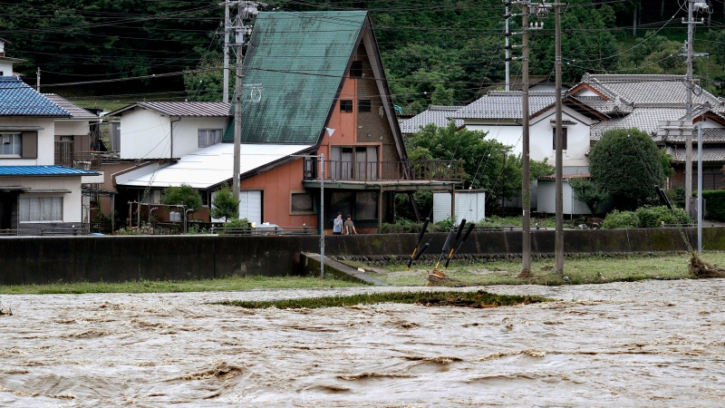 People look at swollen Hida river following heavy rain in Gero, Gifu prefecture, southern Japan Wednesday, July 8, 2020. Floodwaters flowed down streets in southern Japanese towns hit by heavy rains. (Yuya Shino/Kyodo News via AP)