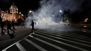 Protesters run from tear gas in front of the parliament building in Belgrade, Serbia, Tuesday, July 7, 2020. (AP Photo/Darko Vojinovic)