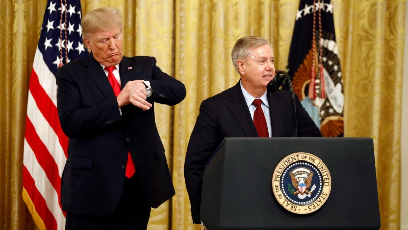 U.S. President Donald Trump pretends to check his watch as Sen. Lindsey Graham, R-S.C., speaks during an event in the East Room of the White House about Trump's judicial appointments, on Nov. 6, 2019. (Patrick Semansky / AP)