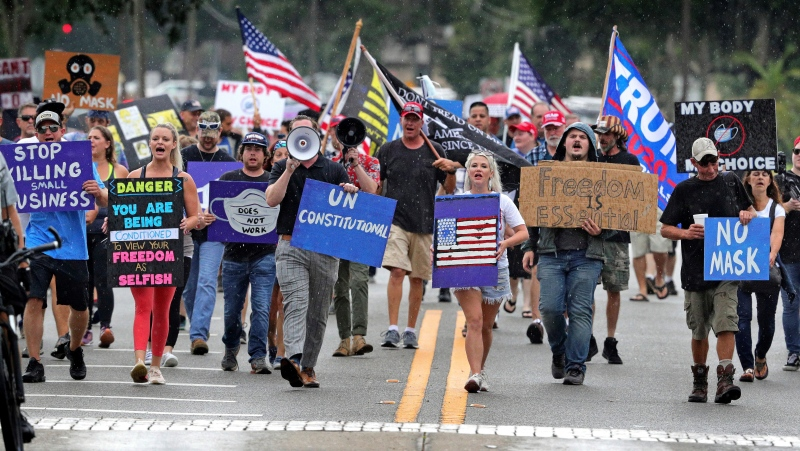 Demonstrators march through downtown Sanford, Fla., Wednesday, July 1, 2020, to protest a Seminole County order requiring people to wear masks in response to the spike in coronavirus cases. (Joe Burbank/Orlando Sentinel via AP)