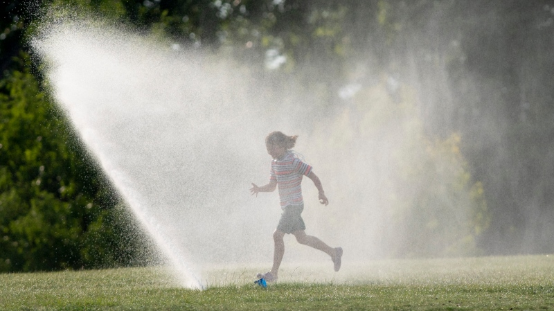 Josephine Young runs through a sprinkler as she takes a break from a bike ride near the Ottawa river Tuesday, July 7, 2020 in Ottawa. The region is under a heat warning this week as humidity and hot temperatures pushed humidex values close to 40C.  (Adrian Wyld/THE CANADIAN PRESS)