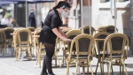 A woman wears a face mask and shield as she cleans a table at an outdoor terrace in Montreal, as the COVID-19 pandemic continues in Canada and around the world. THE CANADIAN PRESS/Graham Hughes