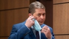 Leader of the Opposition Andrew Scheer removes a face mask as he makes his way to the podium for a news conference, Wednesday, July 8, 2020 in Ottawa. THE CANADIAN PRESS/Adrian Wyld