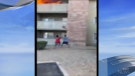 A screenshot of eyewitness video taken on July 3, 2020, showing Phillip Blanks catching a young boy who was thrown from a third-floor apartment balcony in Phoenix, Ariz., by his mother who was trapped inside the unit that was engulfed in flames. (Credit: KABC)