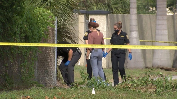 Homicide detectives search a wooded area near the intersection of 38th Avenue South and 31st Street South in St. Petersburg, Fla.