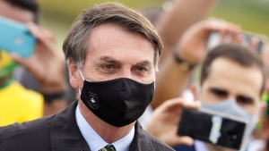 In this May 25, 2020, file photo, Brazil's President Jair Bolsonaro, wearing a face mask amid the coronavirus pandemic, stands among supporters as he leaves his official residence of Alvorada palace in Brasilia, Brazil. (AP Photo/Eraldo Peres, File)
