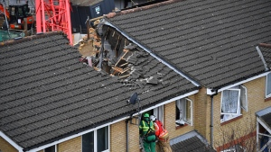 Emergency personnel at the scene in Bow where a 20-metre crane collapsed on to a property leaving people trapped inside, in east London, Wednesday July 8, 2020. (Victoria Jones/PA via AP)